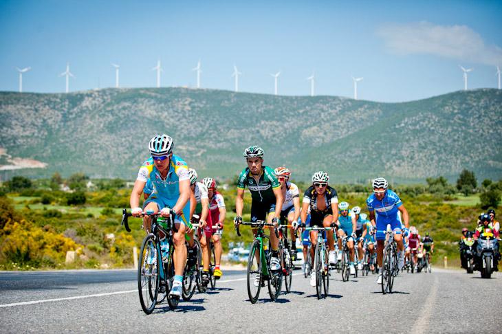 風車の連なるトルコの西部の丘陵地帯を行く選手たち