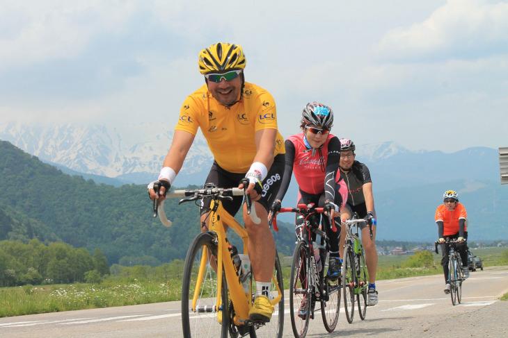 折り返し後は下り基調で楽チンだ。後立山連峰に黄色いメタボ会長が映える!