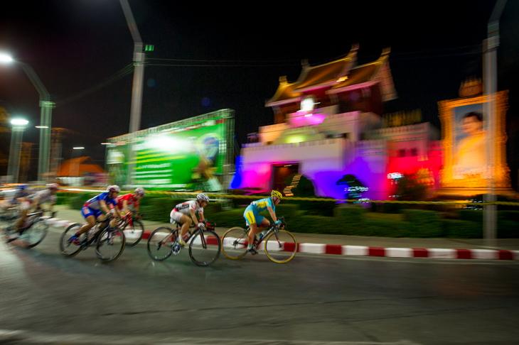 ライトアップされた建造物の前を通過する選手たち