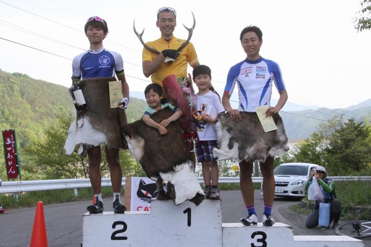 子供たちと一緒に表彰台に上る総合優勝の高岡亮寛(イナーメ)、2位に間瀬勇毅(京都産業大学)、3位に風間博之(サイクルフリーダム)