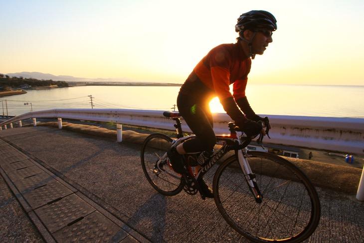 真玉海岸の夕陽を横目に勾配を駆け上がる