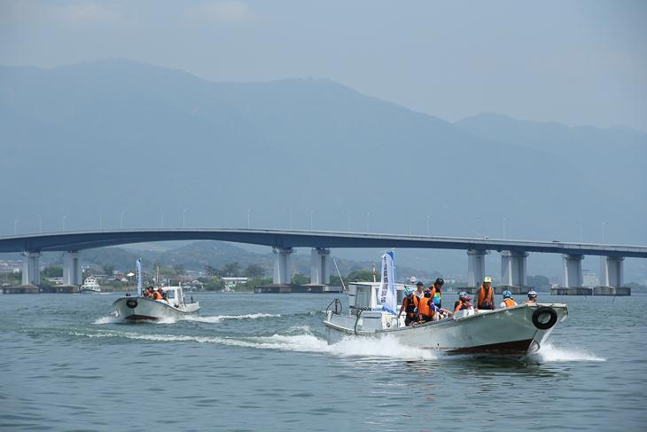 琵琶湖大橋を背後に湖面を快走する漁船タクシー