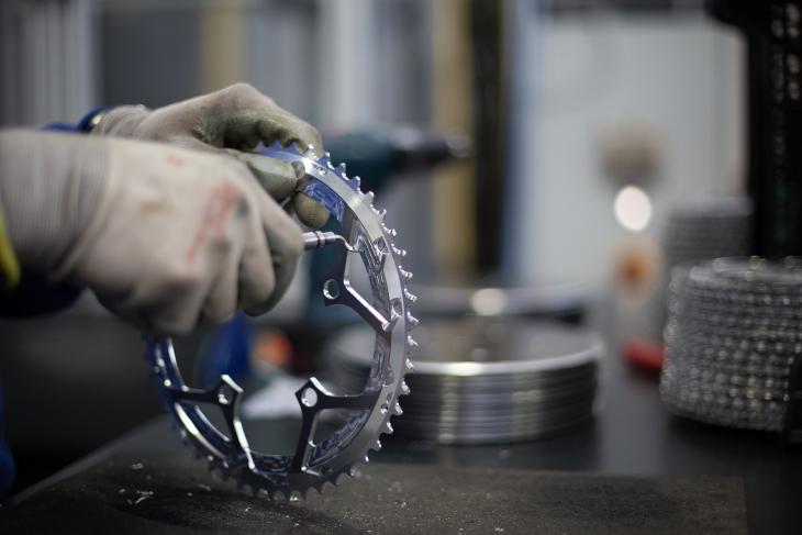 多くの工程が自動で行われるが、バリ取りなどは人の手で行われる