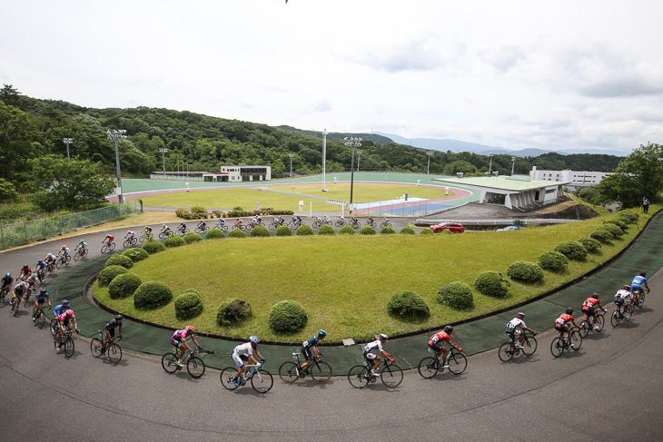 日本競輪学校のトラックを横目に走るメイン集団