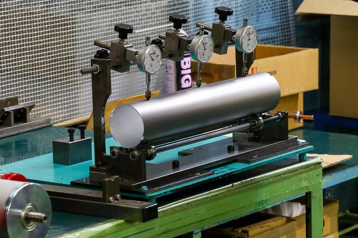 ローラー用パイプの検査。納入されたアルミパイプを回転させて3か所のマイクロメーターで真円度を測定