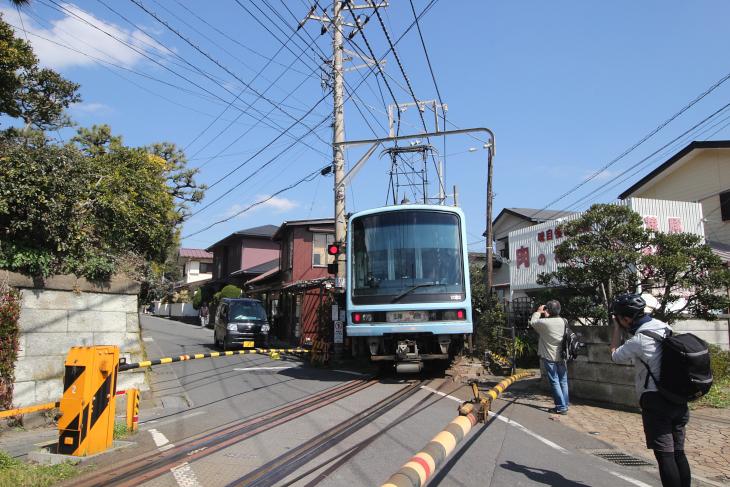 江ノ島電鉄は住宅が立ち並ぶなかを走るため迫力満点だ