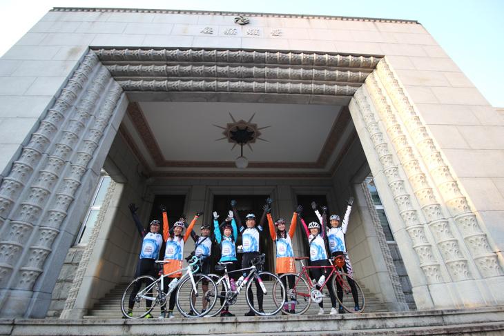 四国一周サイクリングの旅を終えたPR隊が、愛媛県庁のファザードで喜びのポーズ