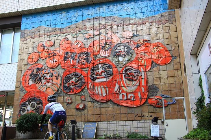 高崎駅の壁には高崎の特産品「縁起だるま」が描かれた壁画がある