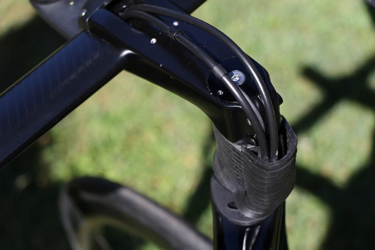 ボルトを外して上部のカバーを取り払うとブレーキホースとDi2ケーブルが露出する。空力性能とメンテナンス性を両立している