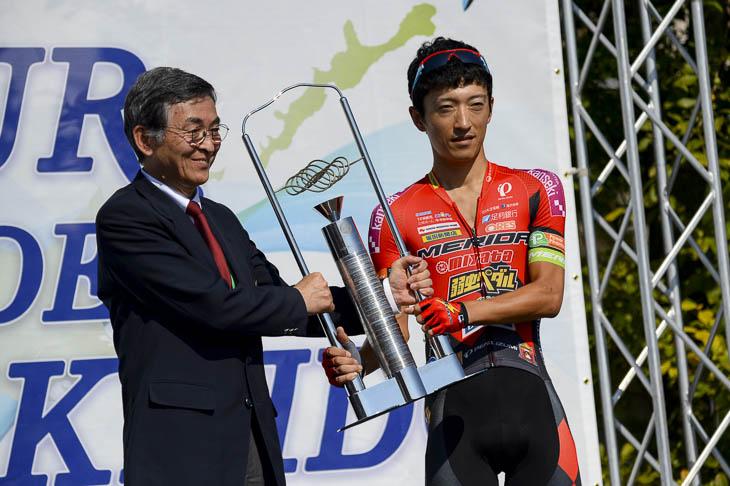 昨年個人総合優勝の増田成幸(宇都宮ブリッツェン)から、優勝トロフィーが返還される
