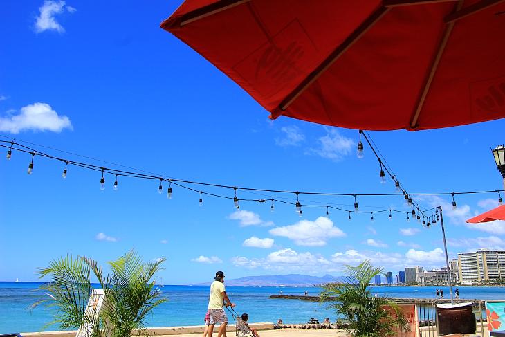 赤いパラソルと青い海のコントラストが美しいベアフットビーチカフェ