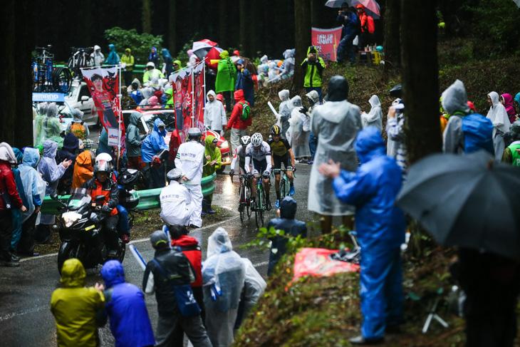 雨具に身を包んだ観客を縫って進むトマ・ルバ(フランス、キナンサイクリング)ら